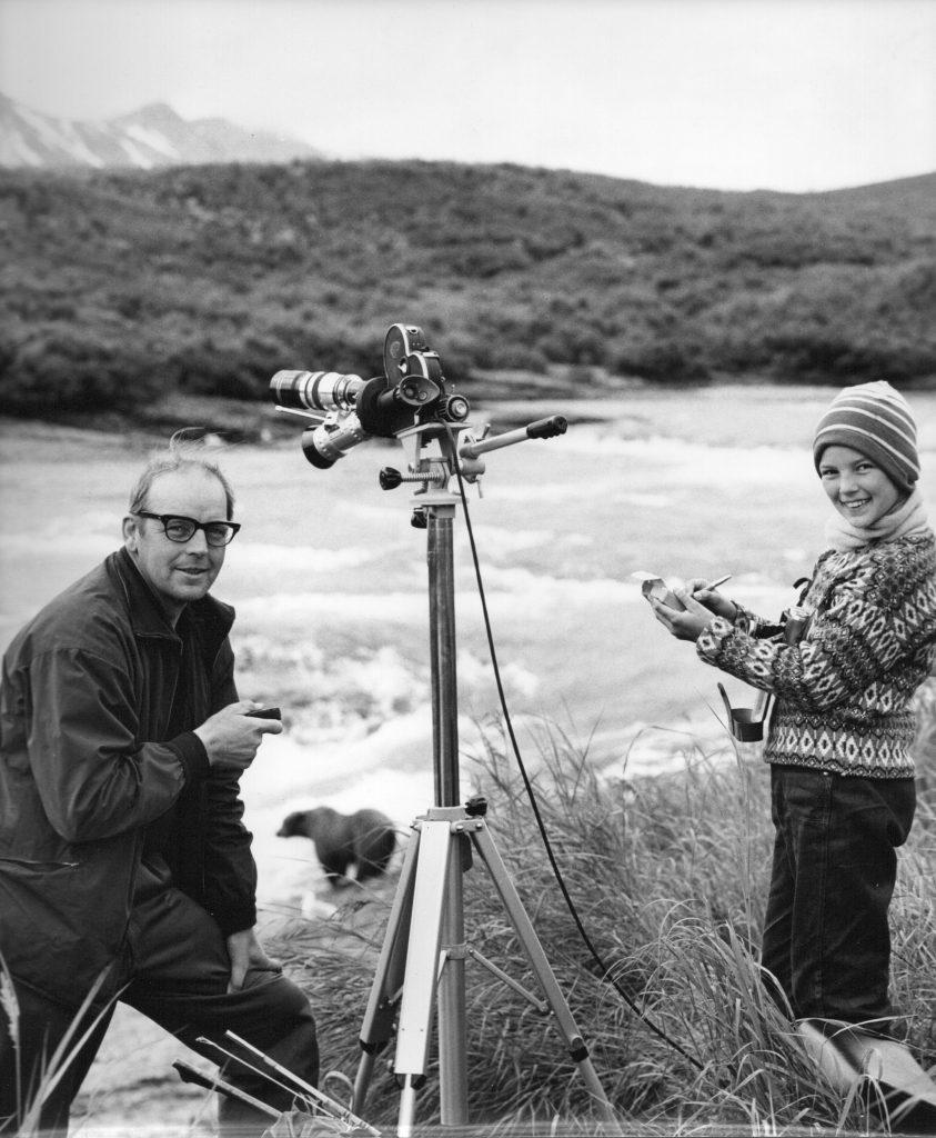 Svartvit bild på Sven och Pia, leendes mot kameran. 1961. En björn fiskar i bakgrunden.